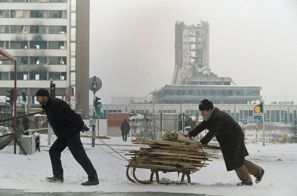 """Mieszkańcy Sarajewa w lutym 1993 roku. W tle zawalony budynek """"Oslobodźenje"""""""