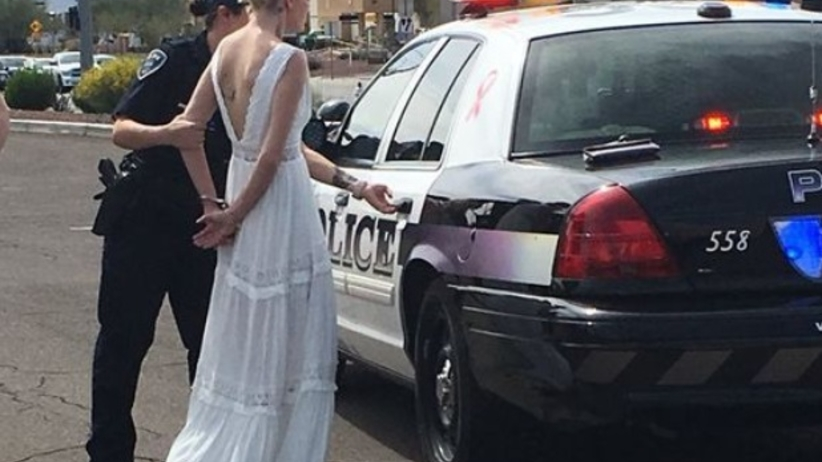 Panna młoda w białej sukni zakuta w kajdanki tuż przed ślubem