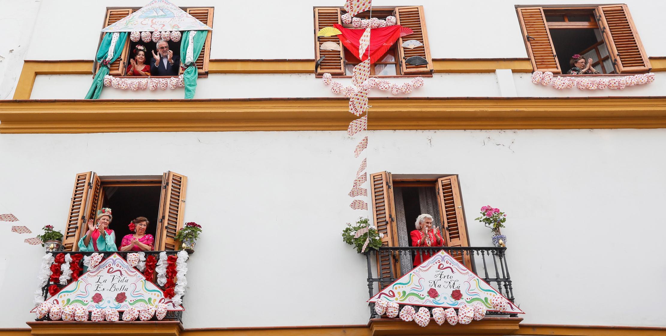Mieszkańcy słynnej dzielnicy Triana w Sewilli, jak każdego dnia, biją brawa z okien i balkonów - tu przyozdobionych z okazji festiwalu Feria de Abril, który miał się właśnie zaczynać.