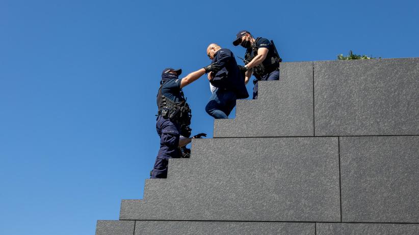 mężczyzna wniósł wieniec na szczyt pomnika smoleńskiego
