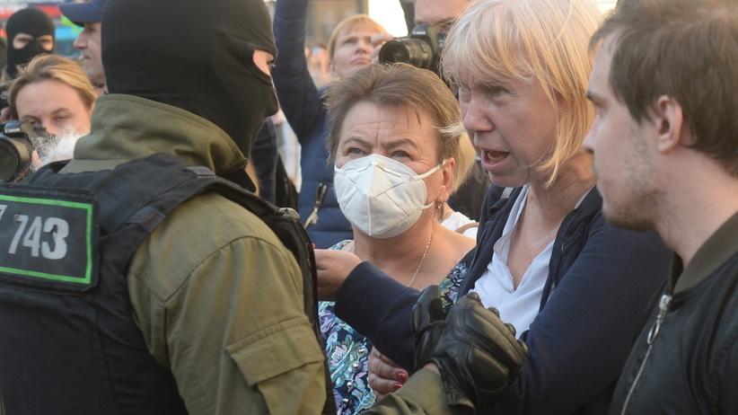 Uczestniczki sobotniego protestu na Białorusi i milicjant