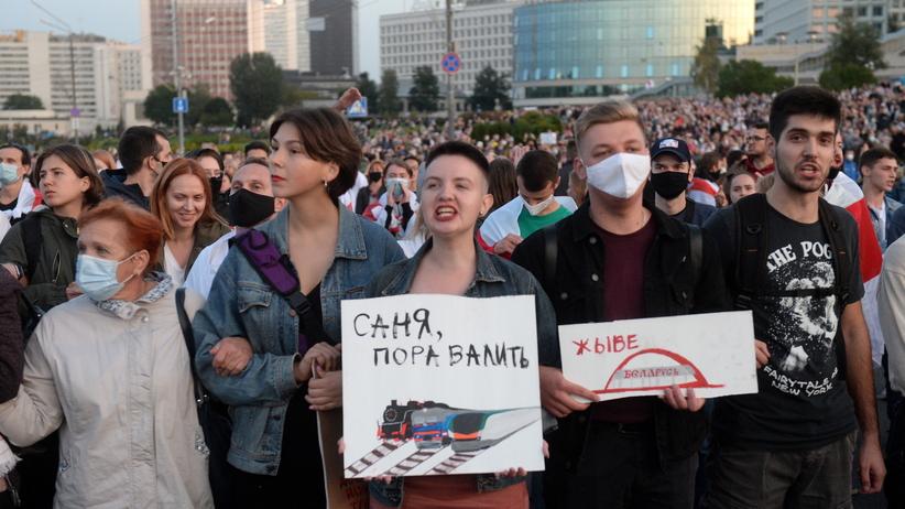 """Zwolennik białoruskiej opozycji trzymający transparent z hasem """"Łukaszenka nie jest moim prezydentem"""""""